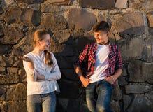 Garçon heureux et fille de sourire posant près du mur en pierre Image stock
