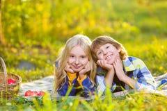 Garçon heureux et fille de sourire se trouvant ensemble sur la couverture Image stock