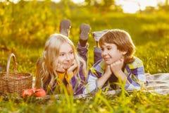 Garçon heureux et fille de sourire se trouvant ensemble sur la couverture Photos stock