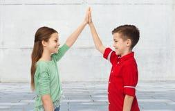 Garçon heureux et fille faisant la haute cinq Photographie stock libre de droits