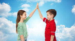 Garçon heureux et fille faisant la haute cinq au-dessus du ciel bleu Photos stock