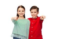 Garçon heureux et fille indiquant le doigt vous Photographie stock