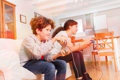 Garçon heureux et fille jouant des jeux vidéo ensemble Photos stock