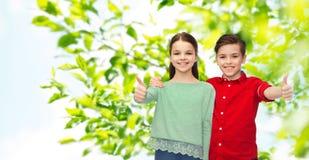 Garçon heureux et fille montrant des pouces  Image libre de droits
