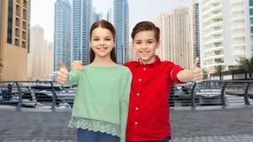Garçon heureux et fille montrant des pouces  Photos libres de droits