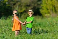 Garçon heureux et fille tenant des mains jouant sur un pré dans le jour ensoleillé photographie stock libre de droits