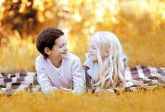 Garçon heureux et petite fille se trouvant sur le plaid ayant l'amusement Image stock