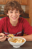 Garçon heureux mangeant de la céréale Image stock