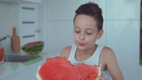 Garçon heureux mangeant de la pastèque rouge et du jus coulant sous les dents banque de vidéos