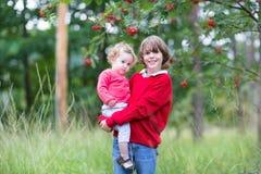 Garçon heureux mignon tenant sa soeur de bébé en parc Images libres de droits