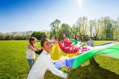Garçon heureux ondulant le parachute coloré avec des amis Images libres de droits