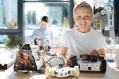 Garçon heureux posant avec ses modèles de robot Images stock