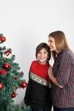 Garçon heureux regardant au camerabeside l'arbre de Noël Photographie stock