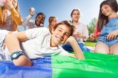 Garçon heureux s'étendant sur le tapis coloré en parc Photo stock