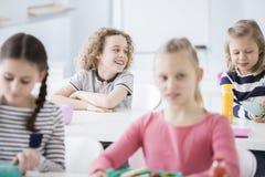 Garçon heureux s'asseyant à la table de salle à manger dans l'école Image libre de droits