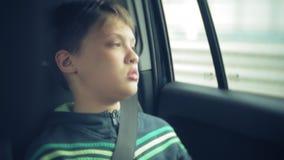 Garçon heureux s'asseyant dans le siège arrière d'une voiture et parlant au téléphone banque de vidéos