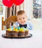 Garçon heureux s'asseyant en Front Of Birthday Cake Photographie stock
