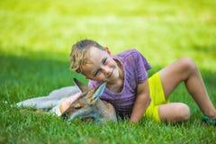 Garçon heureux s'asseyant sur la terre et le kangourou australien de caresse Photographie stock libre de droits