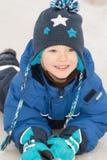 Garçon heureux se situant dans une neige Image libre de droits