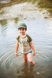 Garçon heureux se tenant dans l'étang Images stock