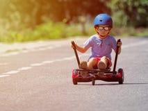 Garçon heureux se tenant sur le hoverboard ou le gyroscooter avec l'accès de kart Photo libre de droits