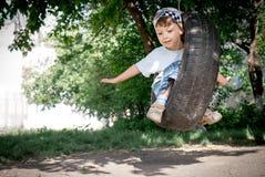 Garçon heureux sur l'oscillation Photographie stock libre de droits