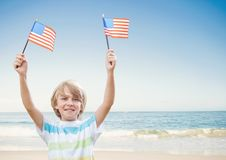 Garçon heureux tenant des drapeaux des Etats-Unis dans la plage Photos libres de droits