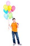 Garçon heureux tenant les ballons colorés Images stock