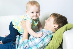 Garçon heureux tenant son bébé de soeur sur le sofa Photographie stock