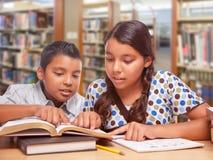 Garçon hispanique et fille ayant l'amusement étudiant ensemble dans la bibliothèque photos libres de droits
