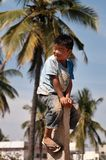 Garçon indien sur le pilier en pierre sur la rue à Bangalore Photographie stock