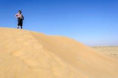 Garçon indien, touriste, avec des jumelles, se tenant sur la dune de sable de Photographie stock libre de droits