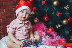 Garçon infantile dans le chapeau rouge de Santa étreignant des jouets sur un fond de l'arbre de Noël et regardant l'appareil-phot Photos stock