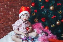 Garçon infantile dans le chapeau rouge de Santa étreignant des jouets sur un fond de l'arbre de Noël et regardant l'appareil-phot Image libre de droits