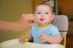 Garçon infantile de bébé heureux mangeant le repas Photos stock