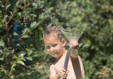 Garçon injectant l'eau d'un tuyau Photographie stock libre de droits