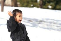 Garçon japonais ayant le combat de boule de neige photographie stock libre de droits