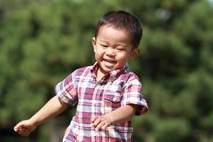 Garçon japonais courant sur l'herbe Image libre de droits