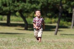 Garçon japonais courant sur l'herbe Photos stock