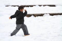 Garçon japonais courant sur le champ de neige Image libre de droits