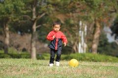 Garçon japonais donnant un coup de pied une boule jaune Photo libre de droits