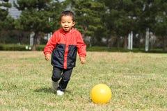 Garçon japonais donnant un coup de pied une boule jaune Photographie stock