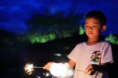Garçon japonais faisant les feux d'artifice tenus dans la main Images stock