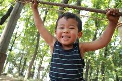 Garçon japonais jouant avec de la corde raide Photo stock