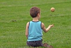 Garçon jetant le base-ball en l'air Photo libre de droits