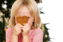 Garçon jetant un coup d'oeil derrière le biscuit de pain d'épice Photographie stock