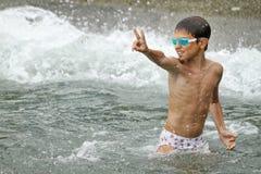 Garçon jouant à la mer Image stock