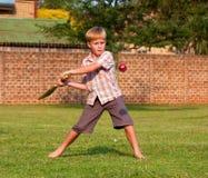 Garçon jouant au cricket en stationnement Image libre de droits