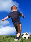 Garçon jouant au football Photo stock