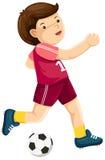 Garçon jouant au football Photos stock